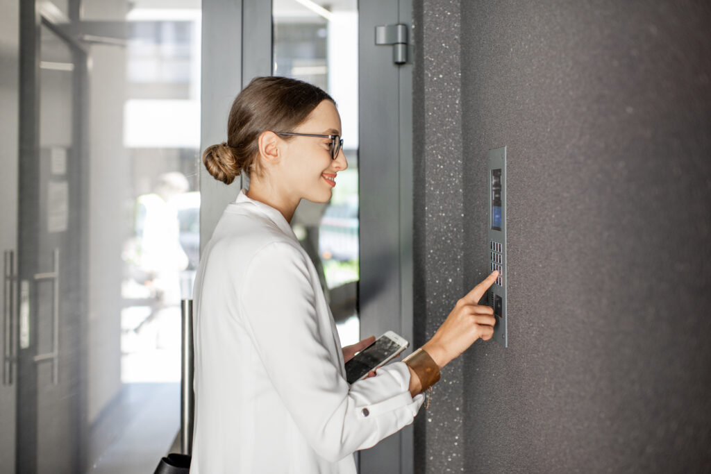 Young business woman in white suit entering code on the intercom keyboard of the residential modern building